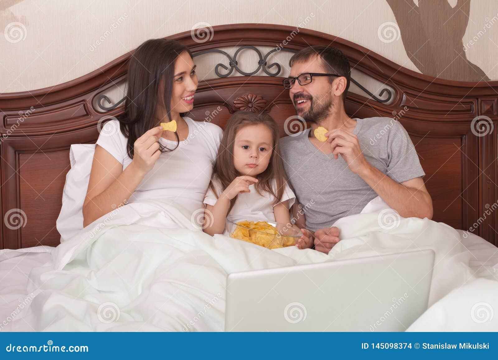 Película de observación de la familia feliz en cama y microprocesadores de la consumición