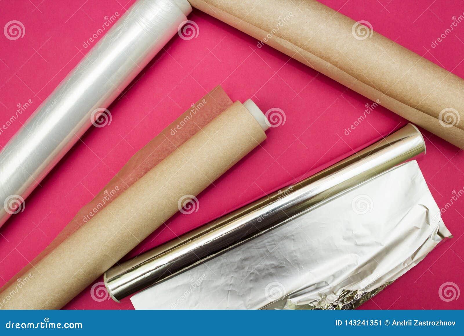 Película de plástico, folha de alumínio e rolo do papel de pergaminho no fundo cor-de-rosa