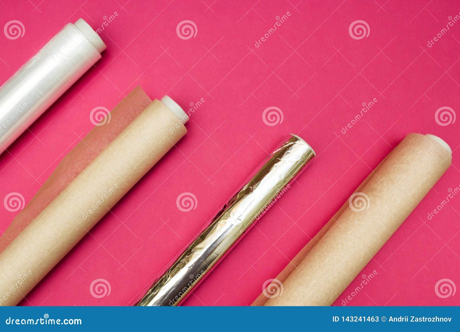 Pel?cula de pl?stico, folha de alum?nio e rolo do papel de pergaminho no fundo cor-de-rosa