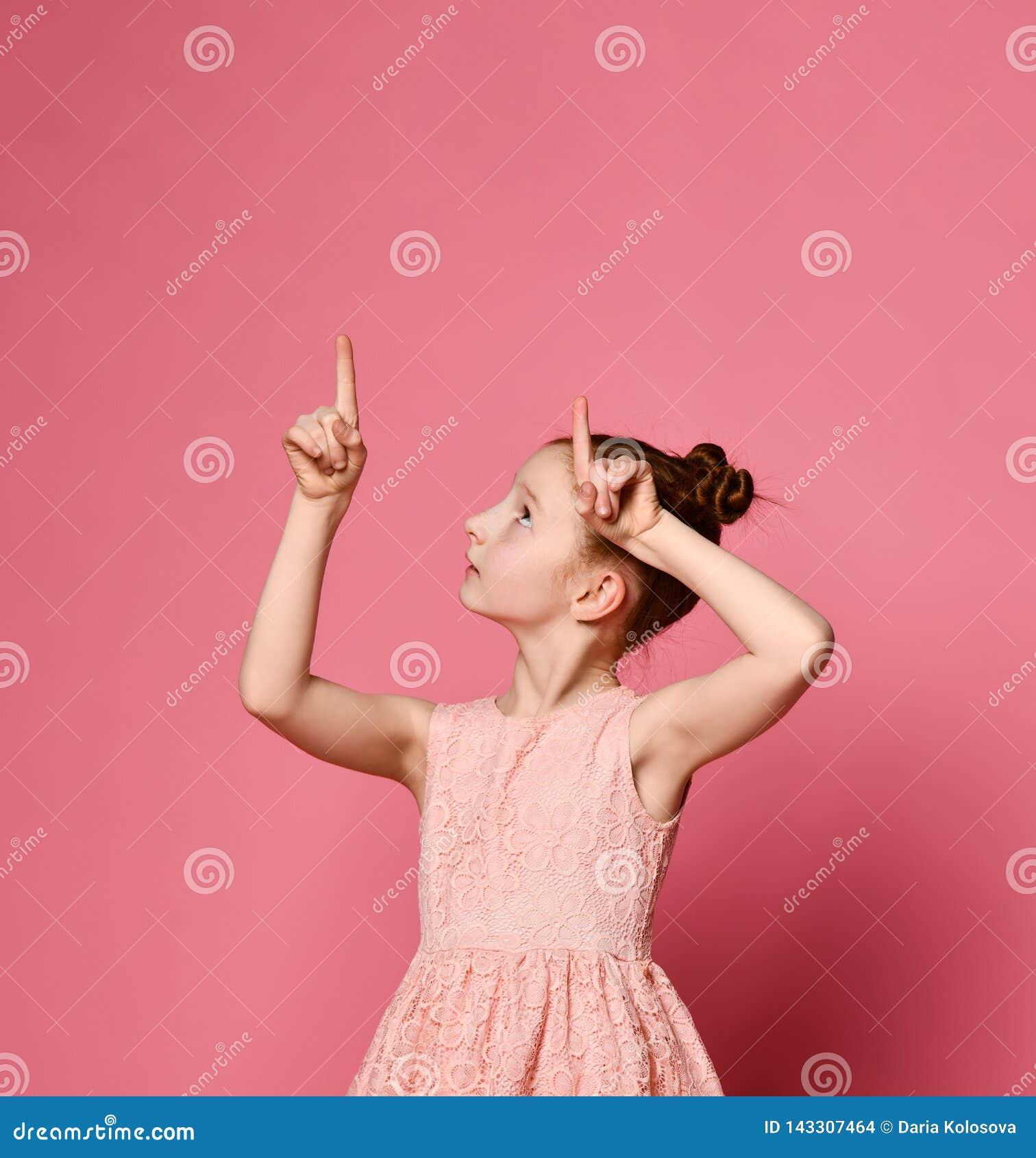 Pelirrojo feliz de la muchacha en el vestido rosado que presenta con la mano en cadera mientras que teniendo una idea y mirando l