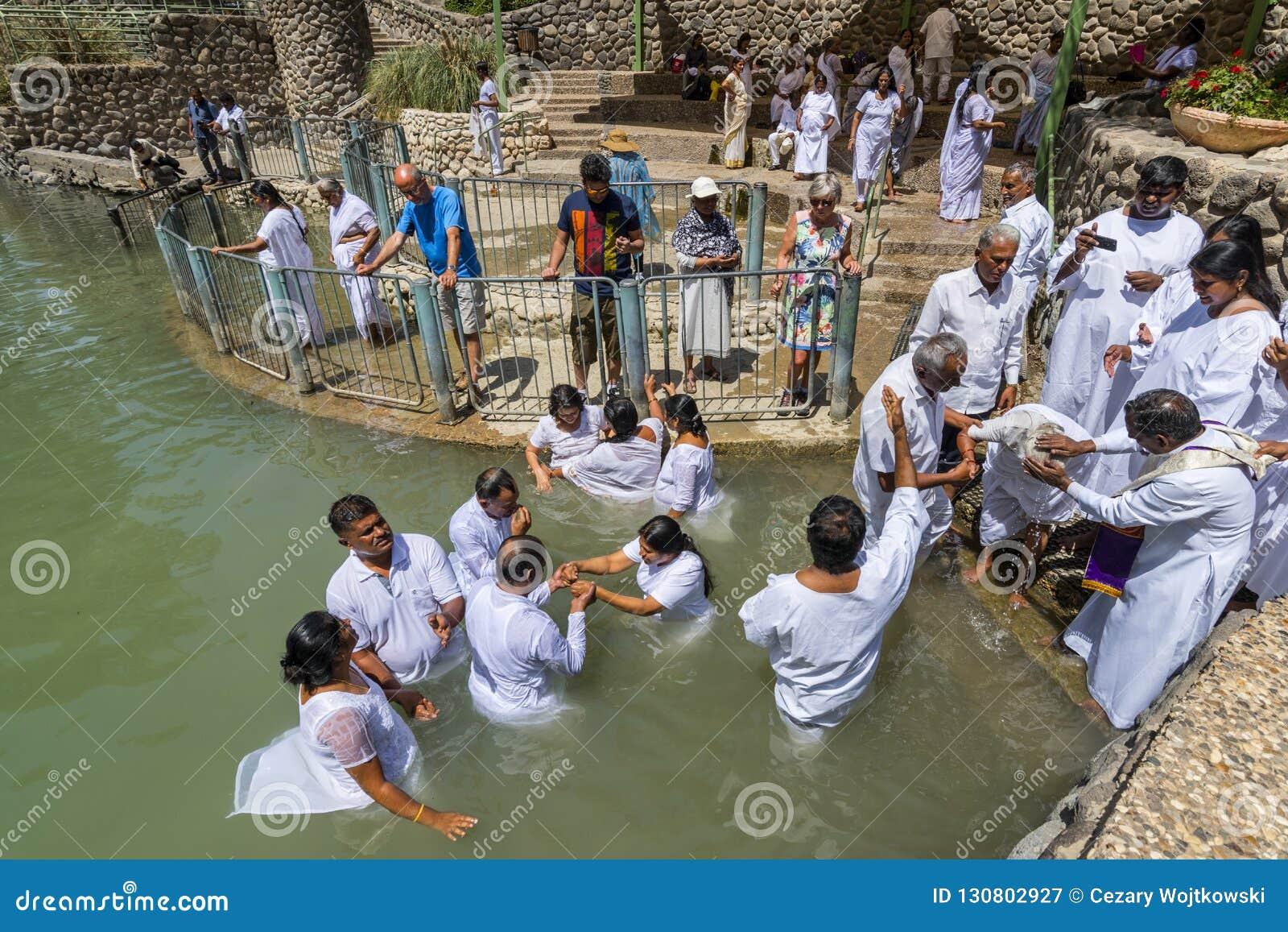 Pellegrini che batezzano in Jordan River, nel sito battesimale di Yardenit L Israele del Nord