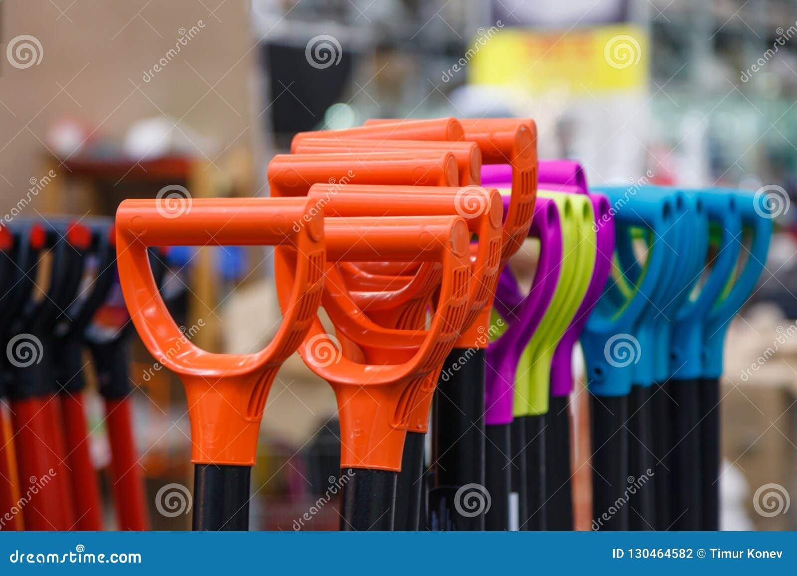 Pelles en plastique colorées à poignée dans les outils de bâtiment de magasin Concentré