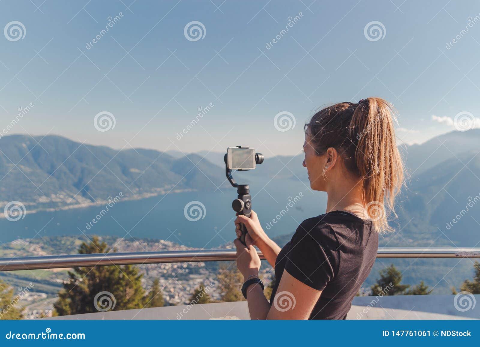 Pelliculage de fille avec le cardan dans les montagnes au-dessus du maggiore de lac