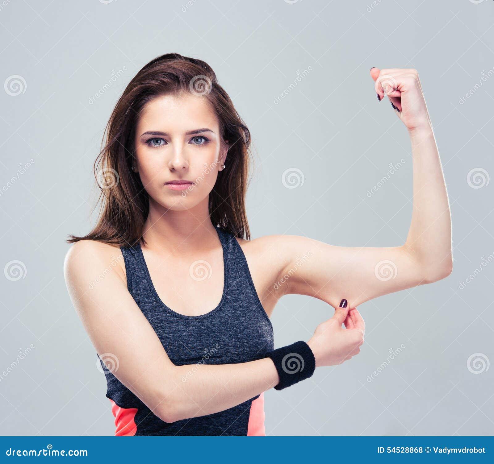 Pellizco de la mujer de la aptitud una grasa en su bíceps