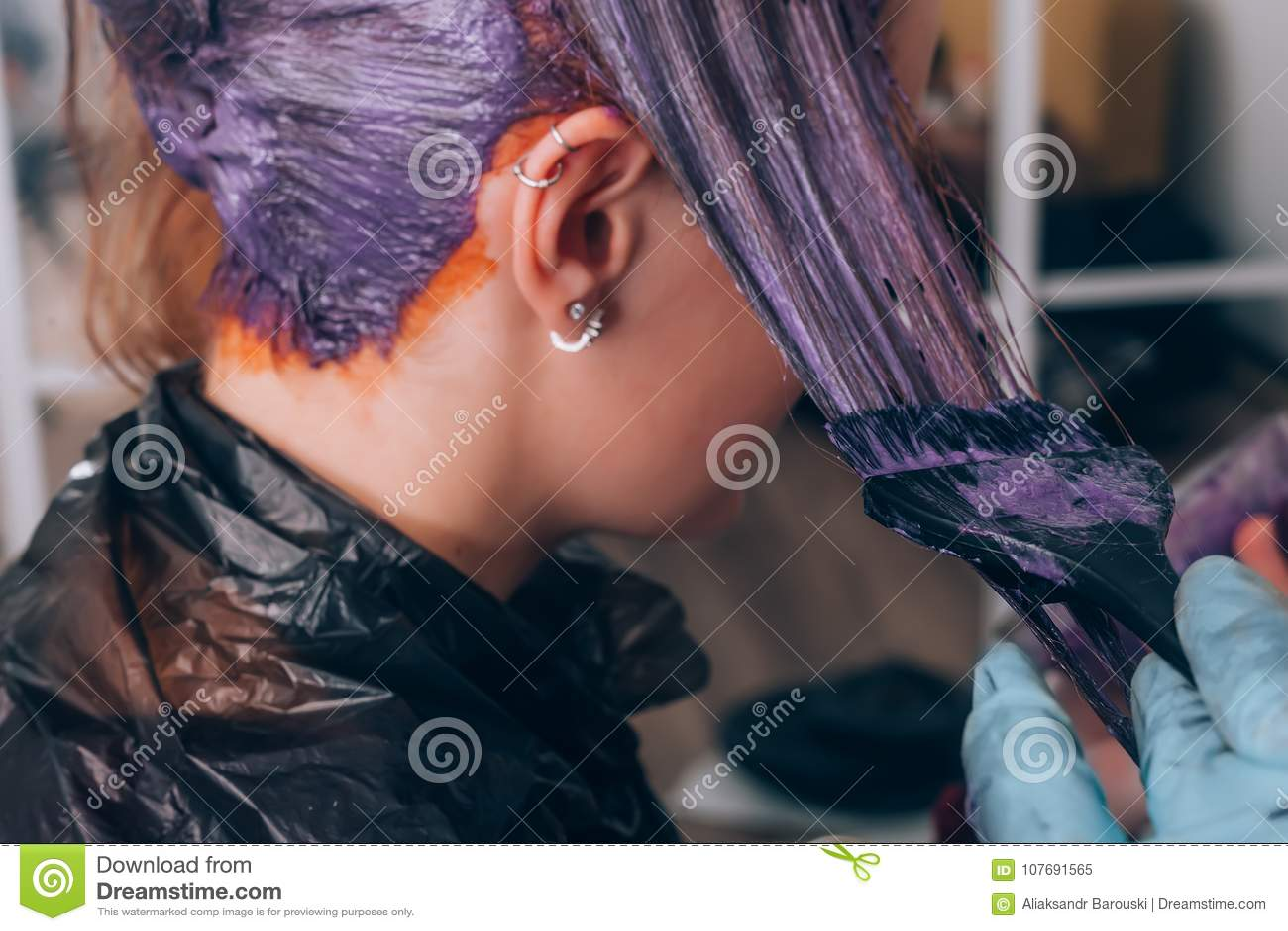 Pelo de teñido del peluquero profesional de su cliente en salón Foco selectivo