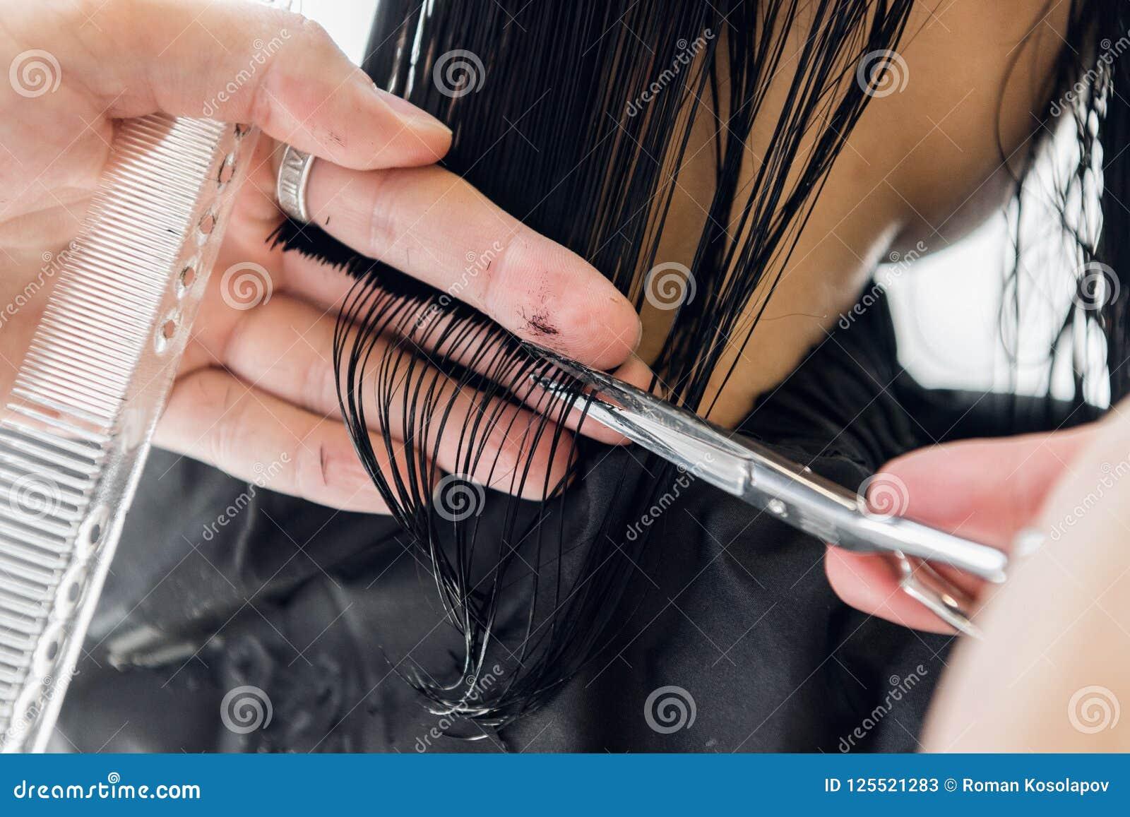 Pelo del ` s del cliente del corte del peluquero en salón con el primer de las tijeras Usando un peine