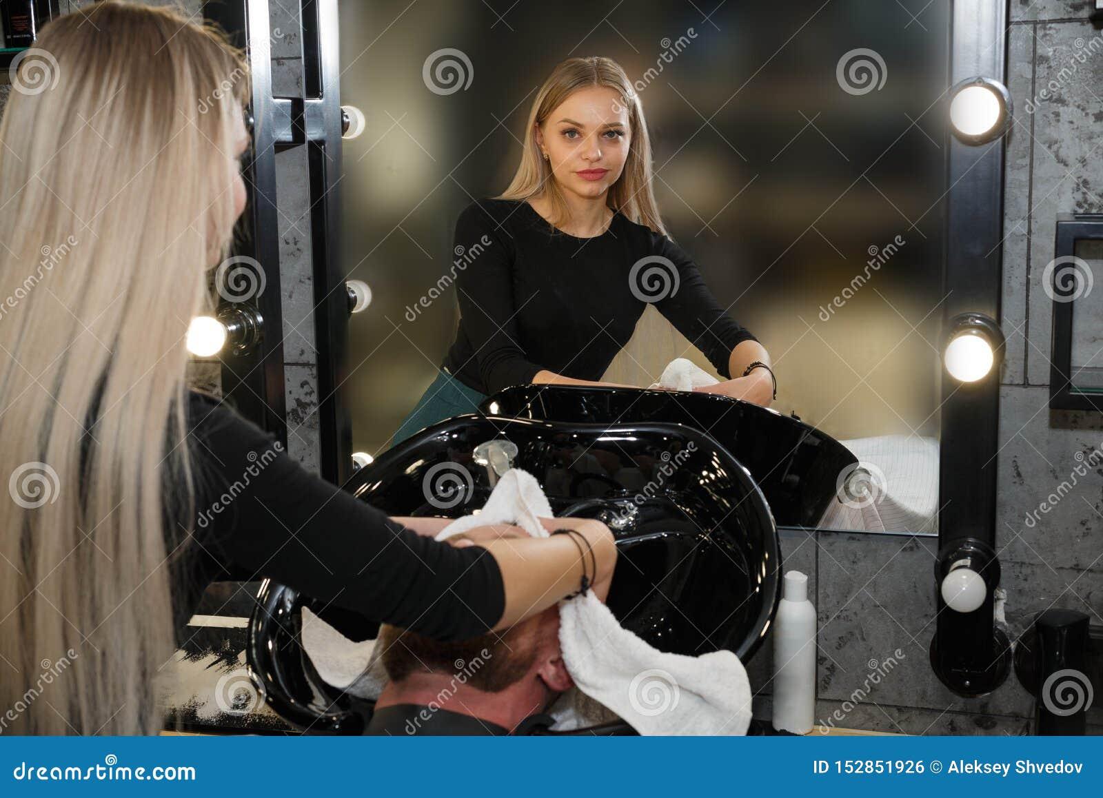 Pelo del ` s del cliente del peluquero que se lava en peluquer?a de caballeros