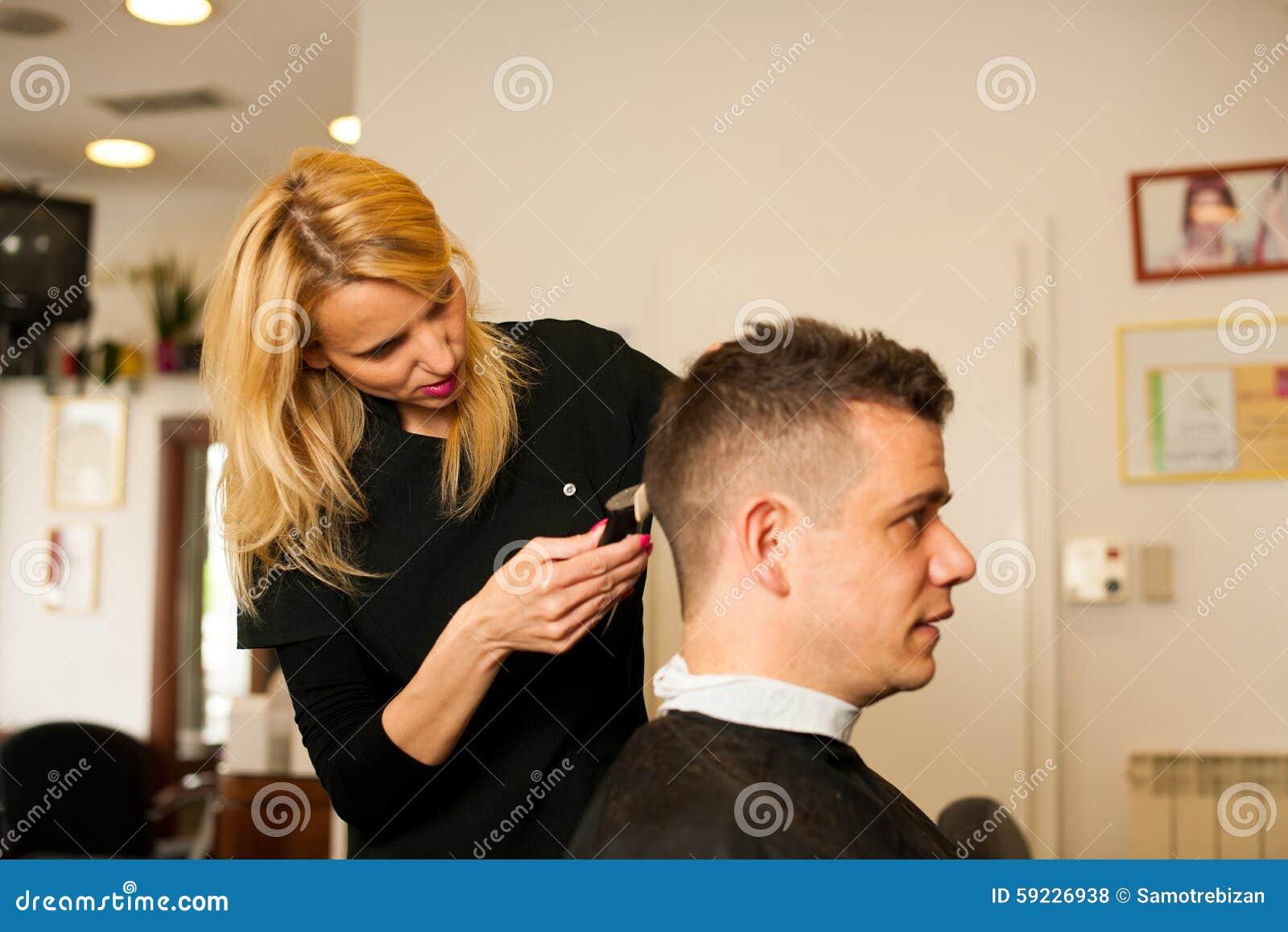 Pelo femenino del corte del peluquero del cliente sonriente del hombre en la belleza