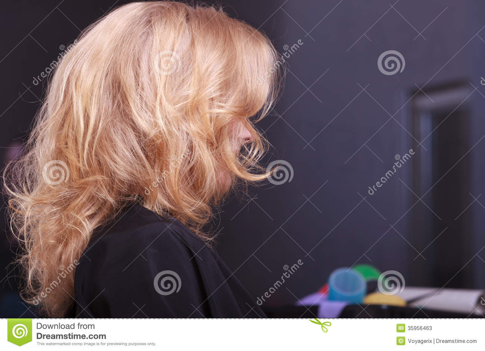 Pelo ondulado rubio femenino. Detrás de la cabeza de la mujer. Peluquero. Salón de belleza.