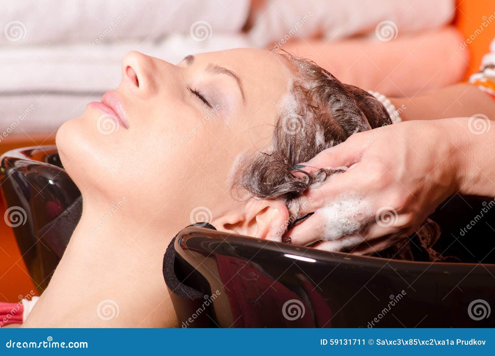 Pelo que se lava de la muchacha en salón de la peluquería