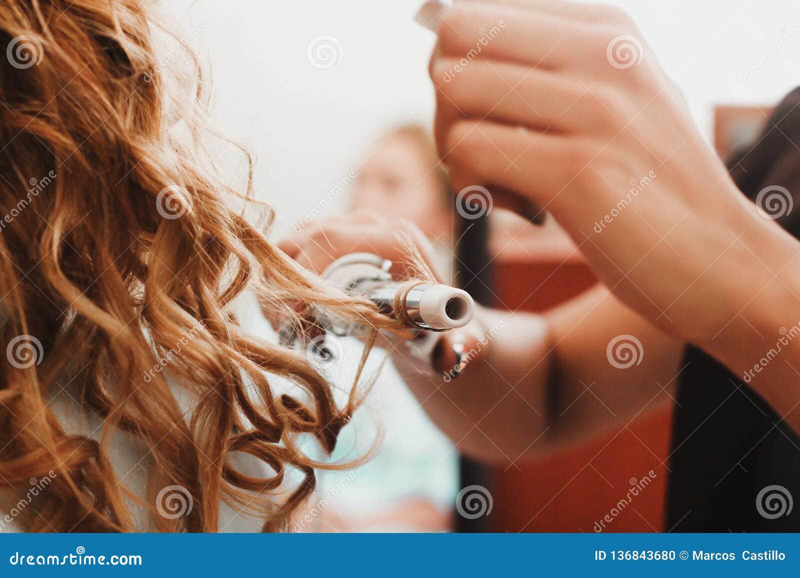 Pelo rizado, mujer con el pelo ondulado rubio largo que lo plancha, usando el hierro que se encrespa, bigudí para los rizos perfe