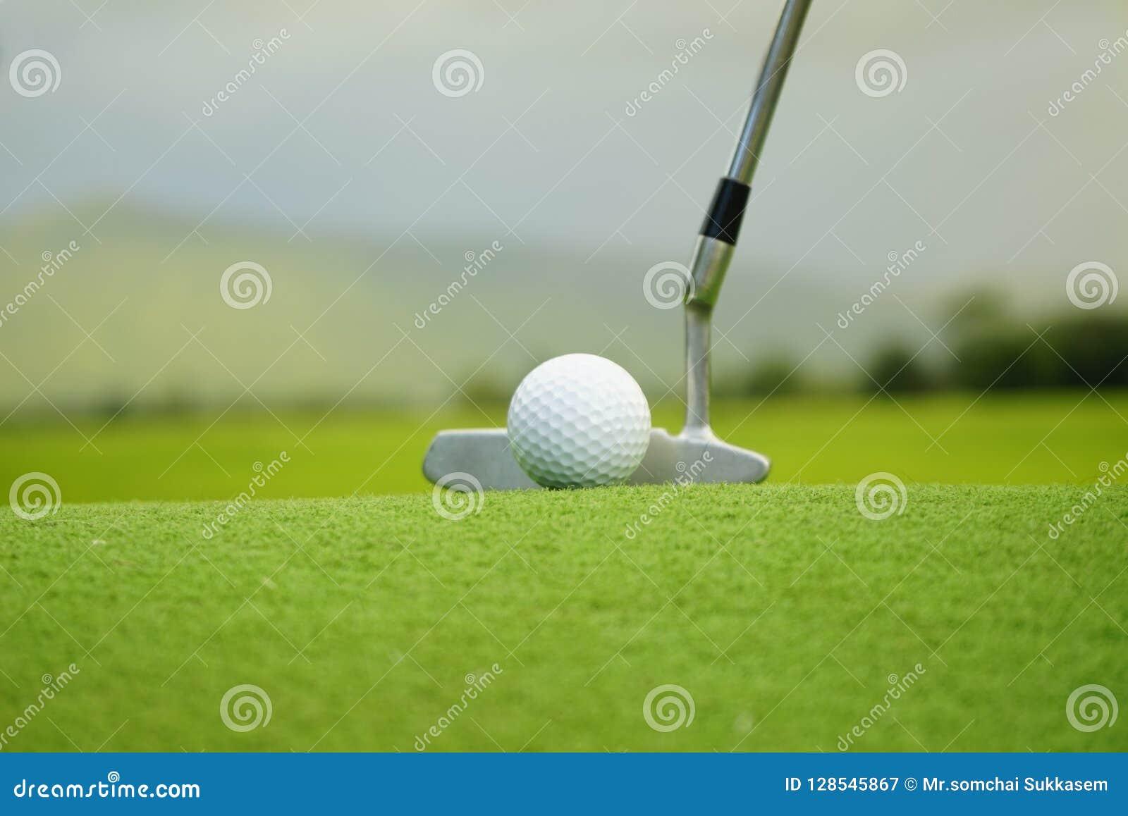 Pelota de golf en camiseta en campo de golf hermoso en el fondo de la puesta del sol