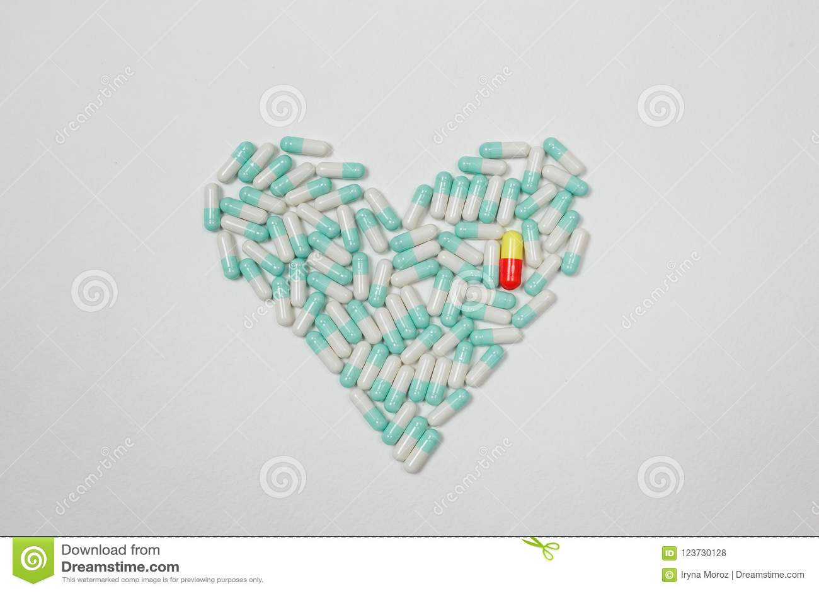 Pelota e tabuletas coloridas das cápsulas da vitamina no fim da tabela acima