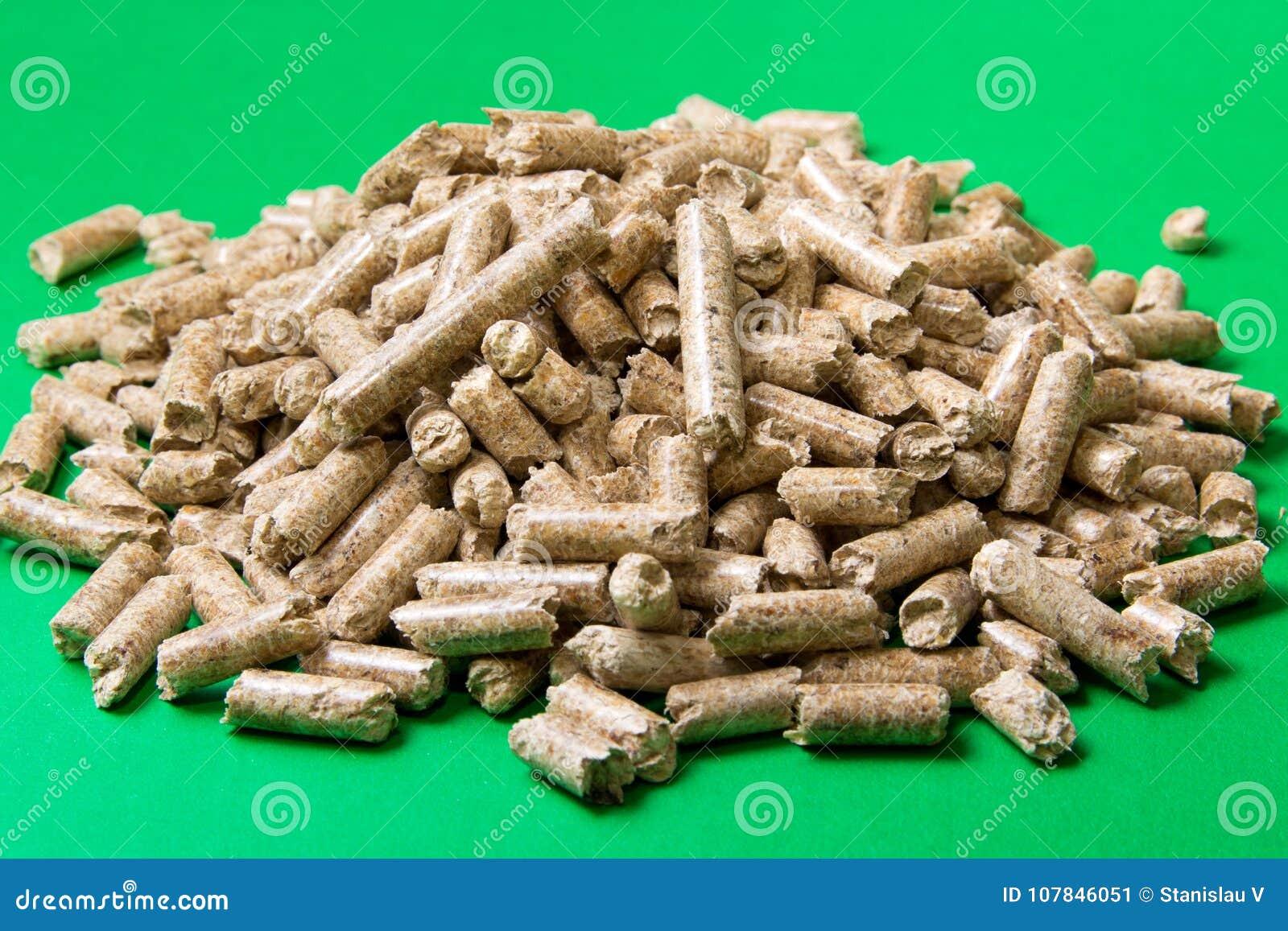 Pelotillas de madera en un fondo verde, espacio de la copia Combustibles biológicos