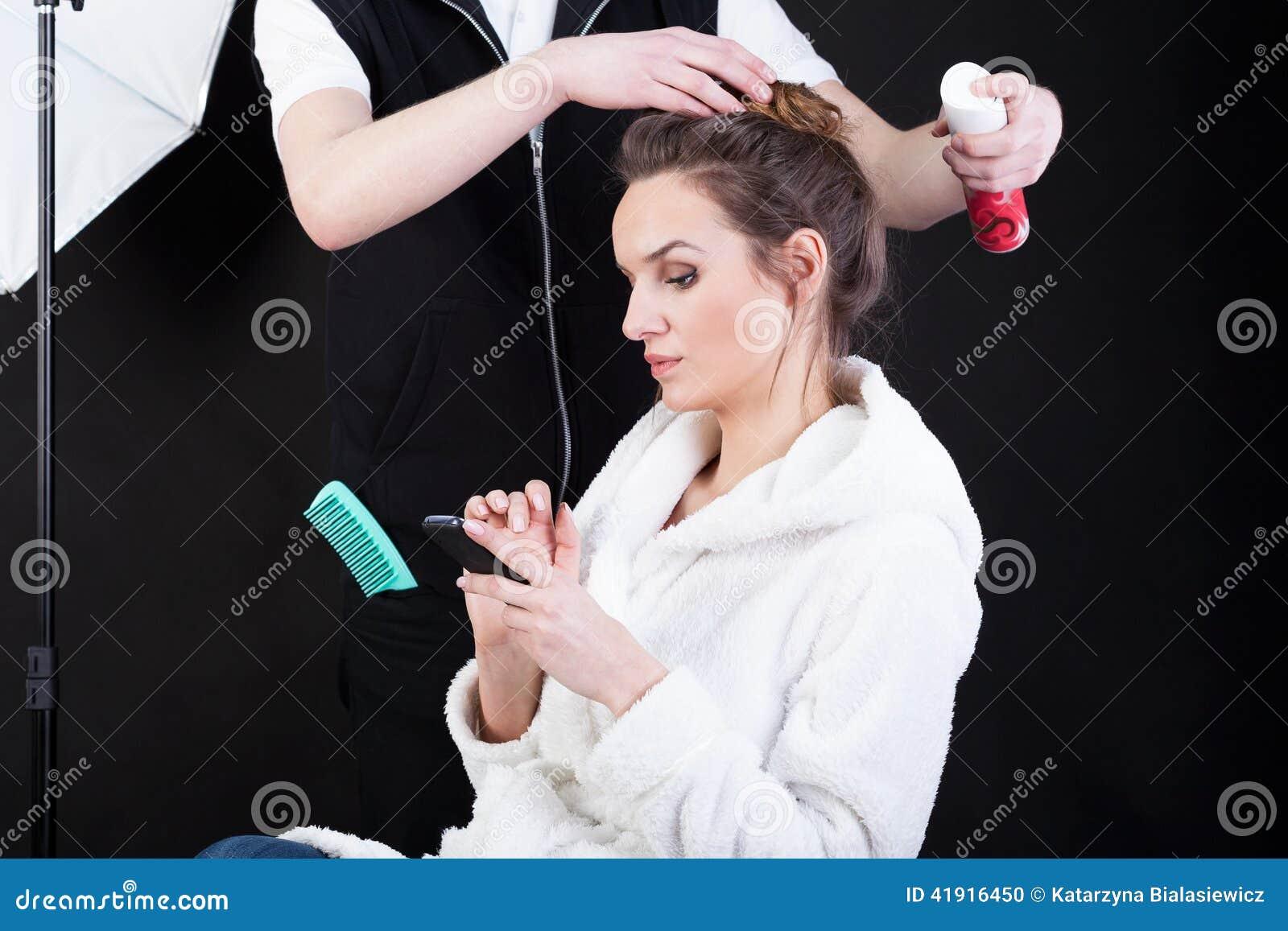 Peluquero que aplica el espray en el pelo del modelo