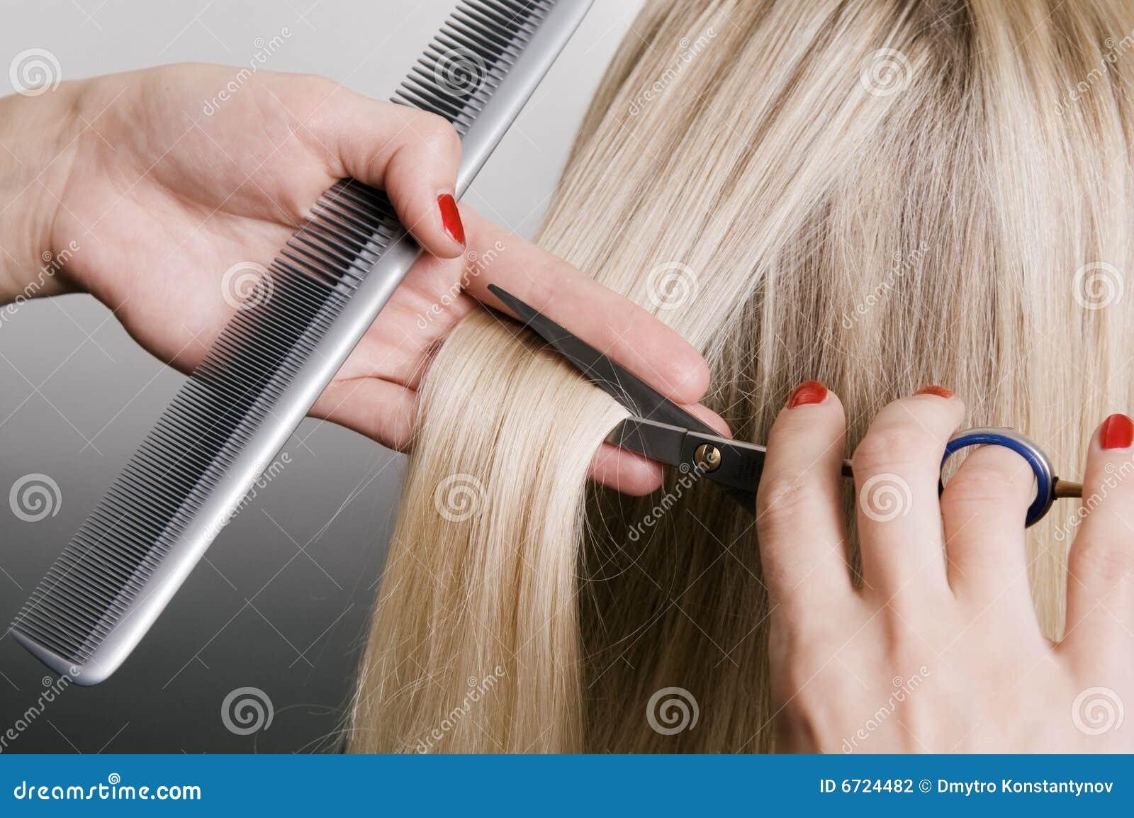 Peluquero que corta el pelo rubio