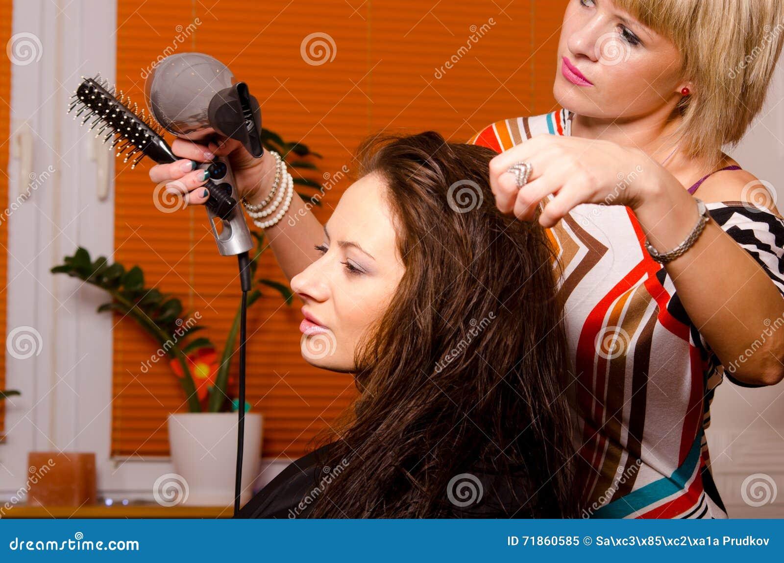 Peluquero que hace el pelo de muchacha feliz hermosa