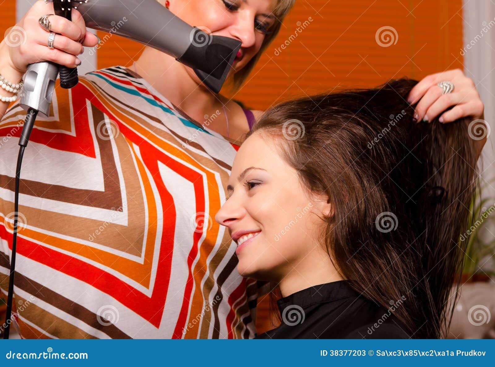 Peluquero que hace el pelo de muchacha hermosa