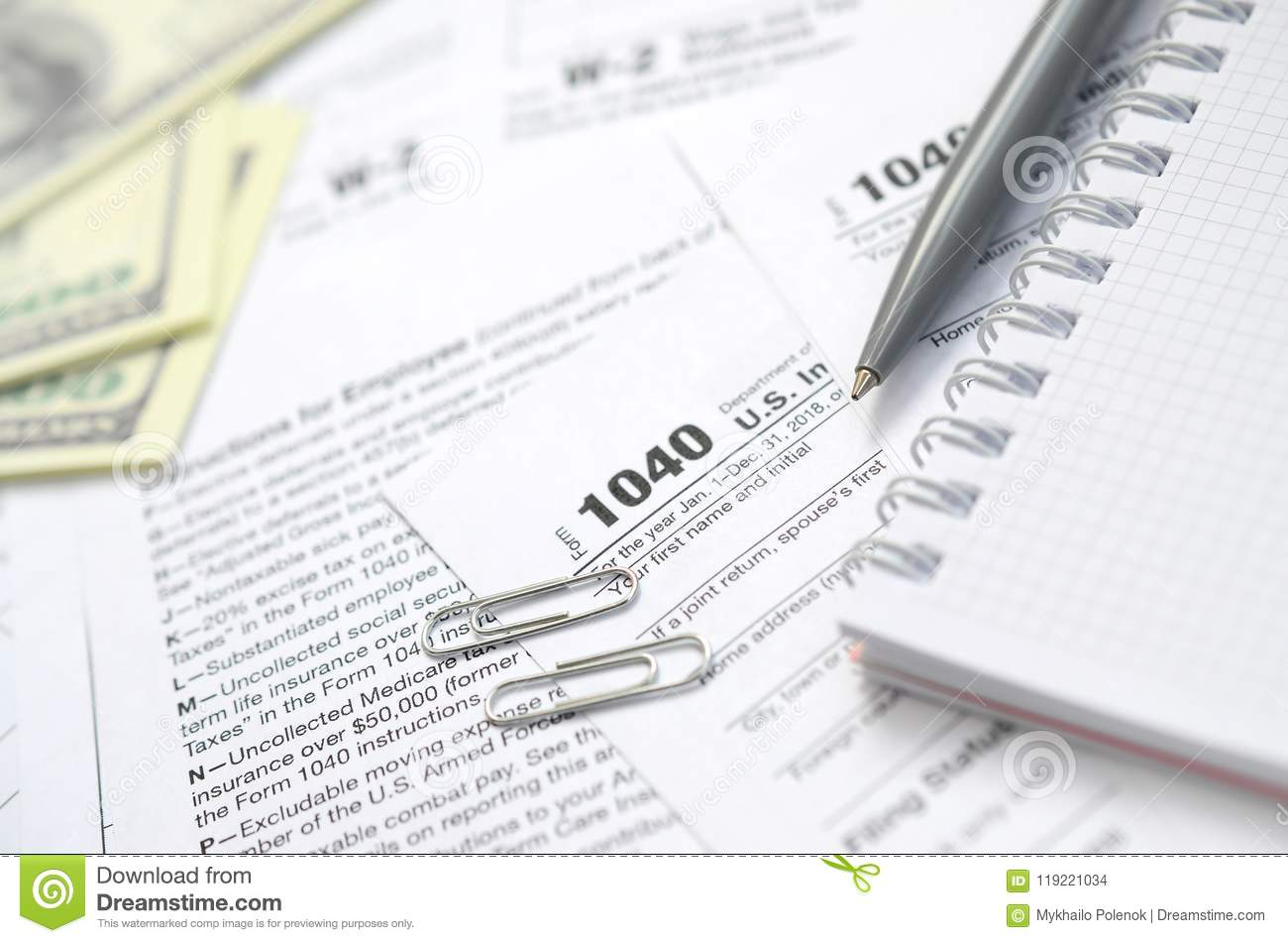 The Pen, Notebook And Dollar Bills Is Lies On The Tax Form 1040