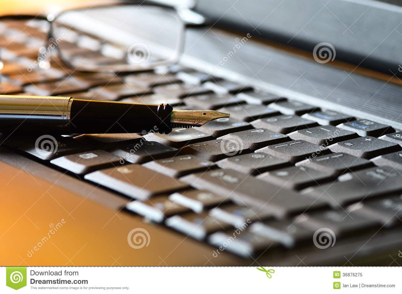 Pen and Reading glasses on a laptop