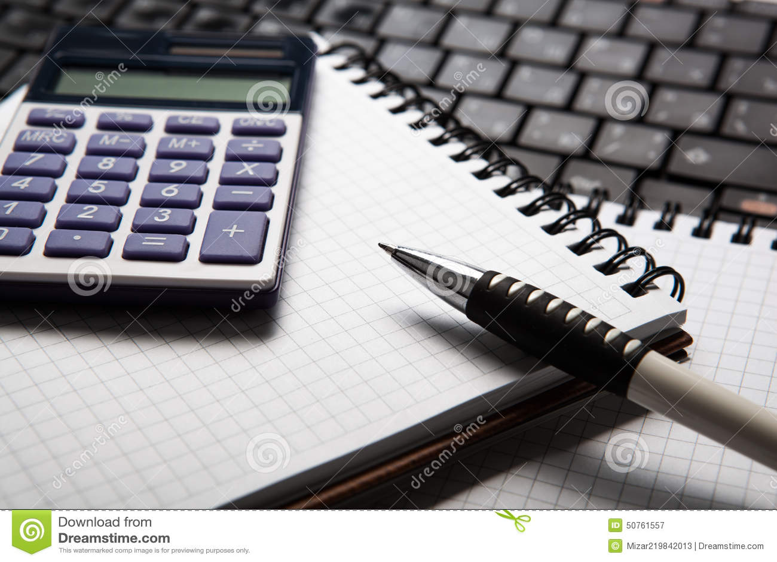 Pena com calculadora em um caderno e em um teclado