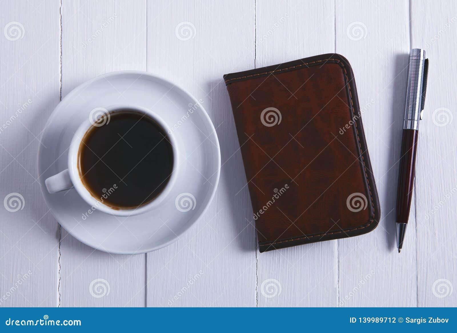 Pena do caderno do café no fundo de madeira