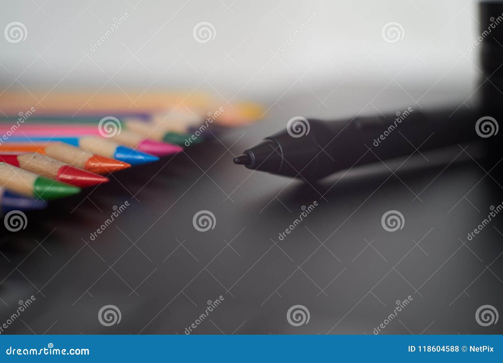 Pena do estilete de Digitas na tabuleta gráfica com os lápis coloridos nos vagabundos