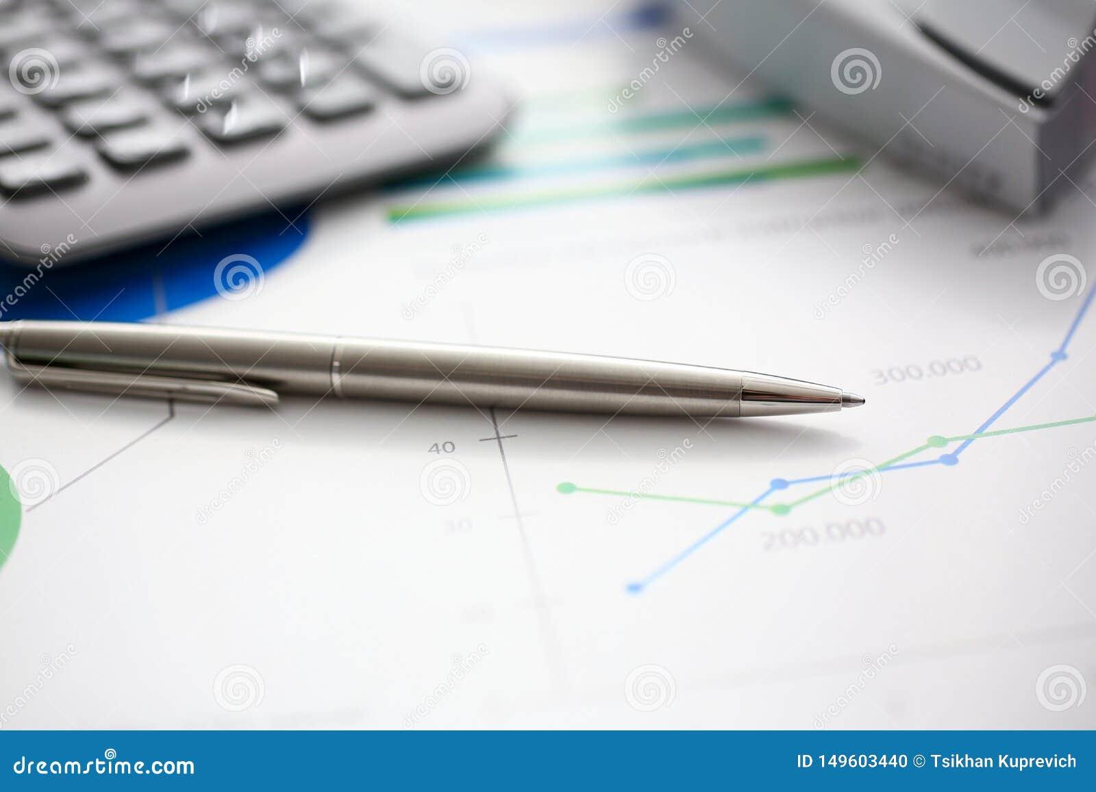 Pena e calculadora de prata no local de trabalho pronto para ser usado