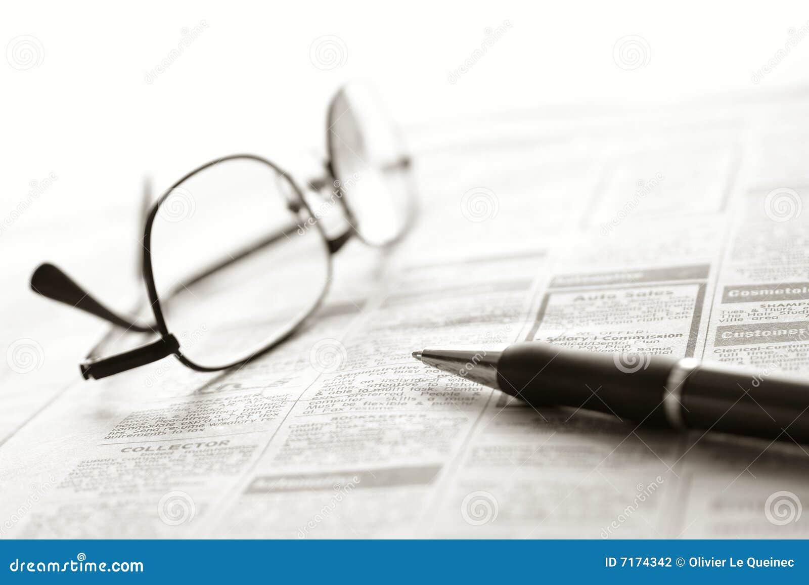 Pena e vidros sobre anúncios classific do jornal