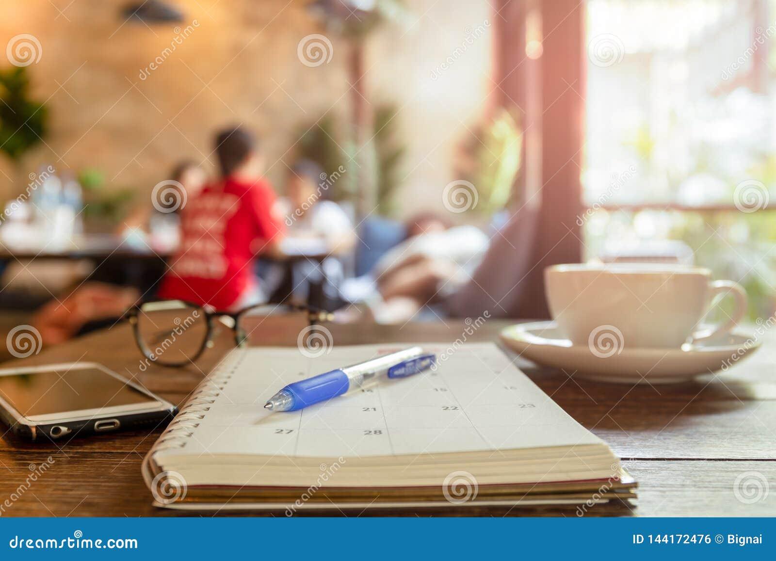 Pena selecionada do foco no livro do calendário com xícara de café e telefone celular