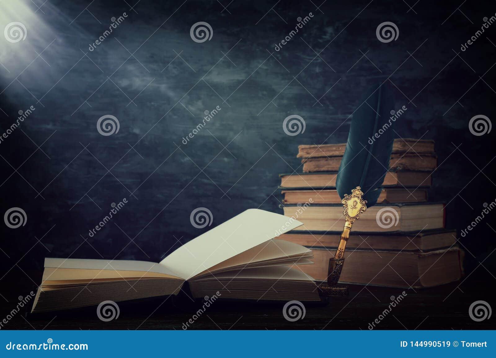 Pena velha da tinta da pena da pena com tinteiro e os livros velhos sobre a mesa de madeira na frente do fundo preto da parede Fo