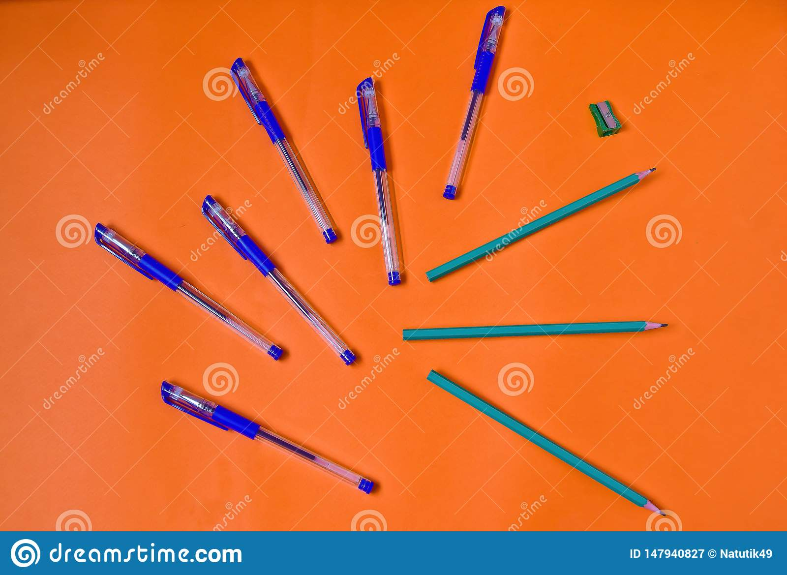 Penas e lápis brilhantes no fundo alaranjado