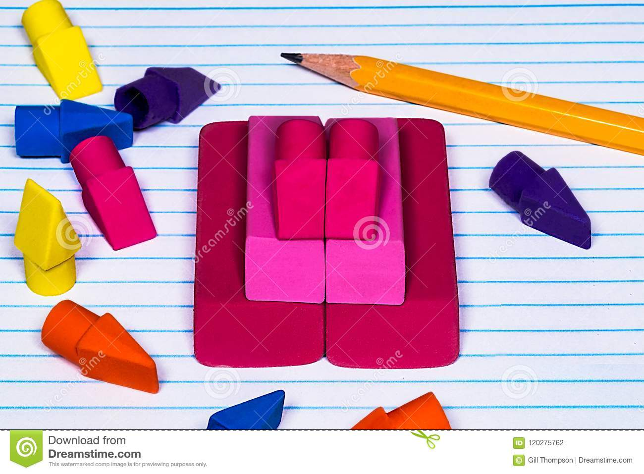 pencil erasers stacked and scattered on college ruled filler pap