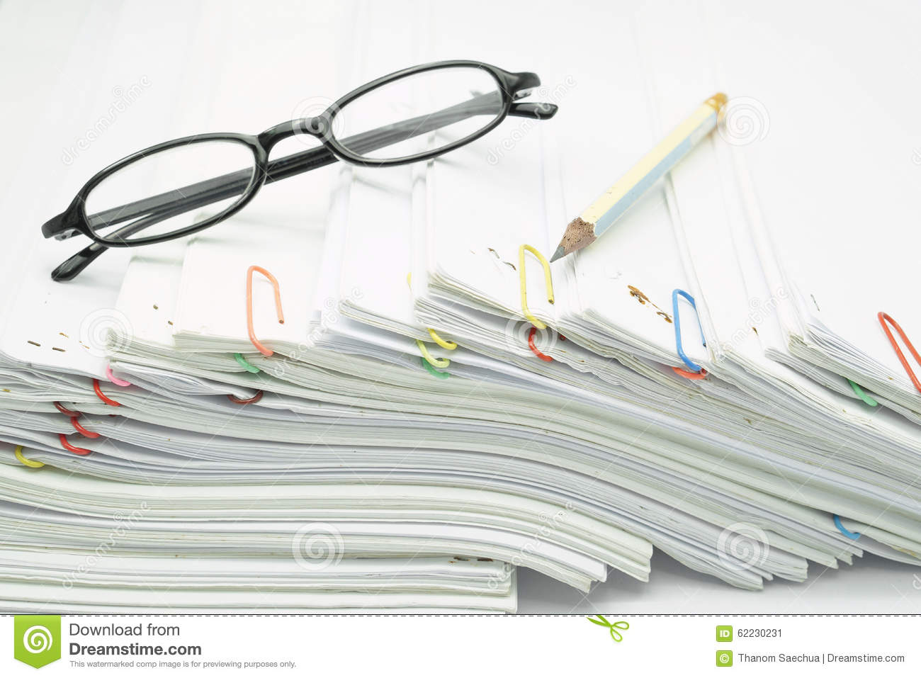 Pile Of Reports : Pencil and spectacles place on pile of overload white