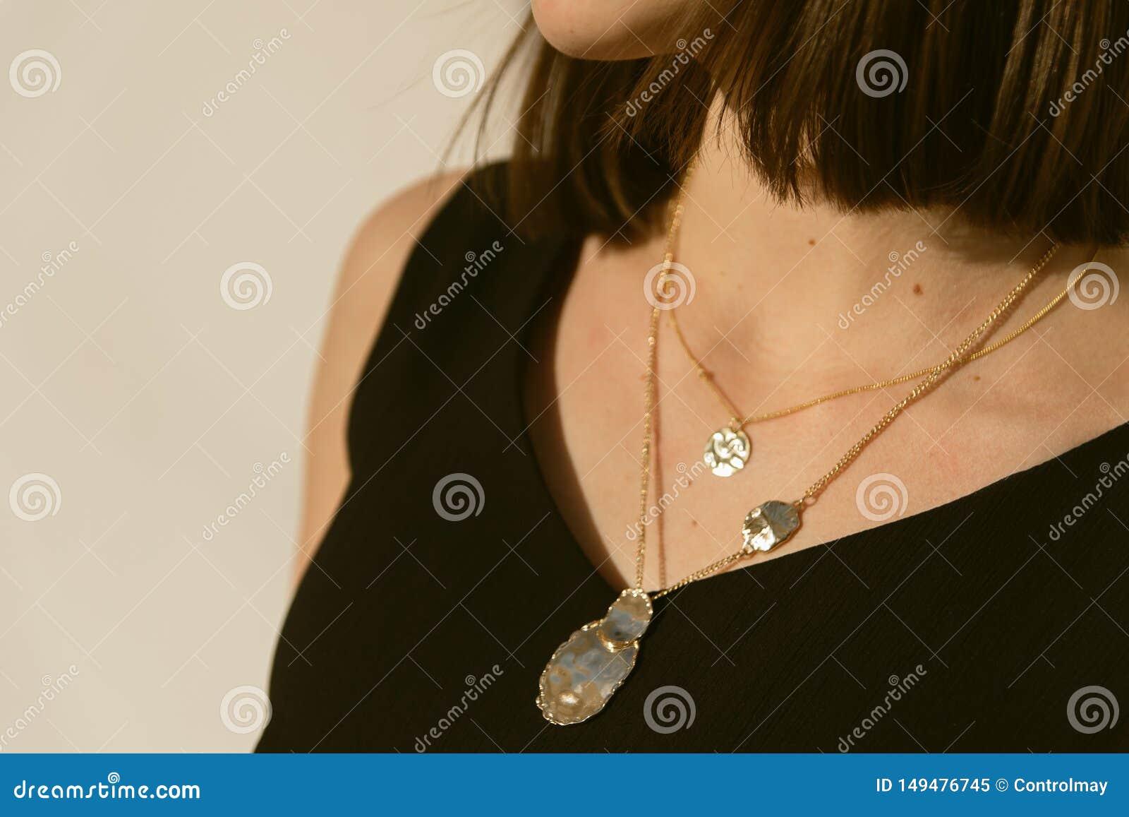 Pendants d or autour du cou d une fille au soleil bijoux élégants de mode sur la personne