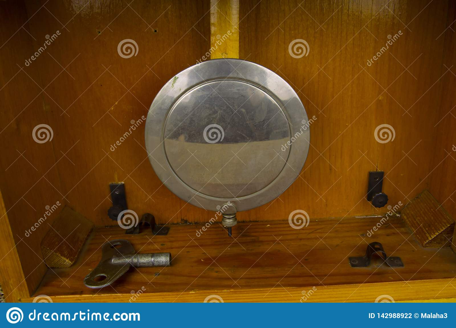 Pendulum of an old clock on a wooden background
