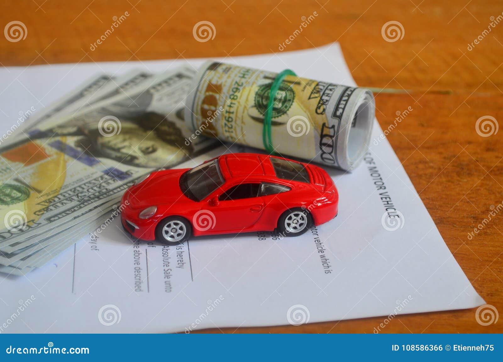 Pengar, köpekontrakt och en röd bil på en trätabell