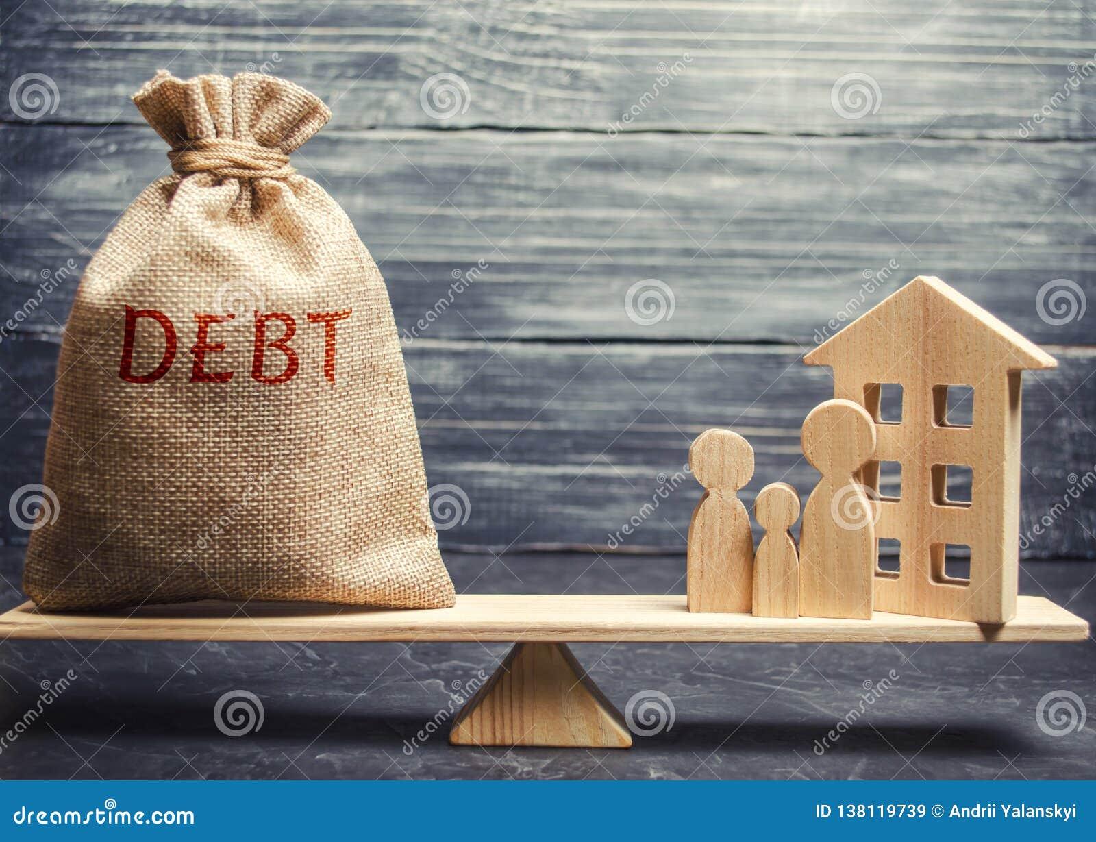 Pengarpåse med ordskulden och ett miniatyrhus med en familj på vågen Betalning av skulden för fastighet Betala av