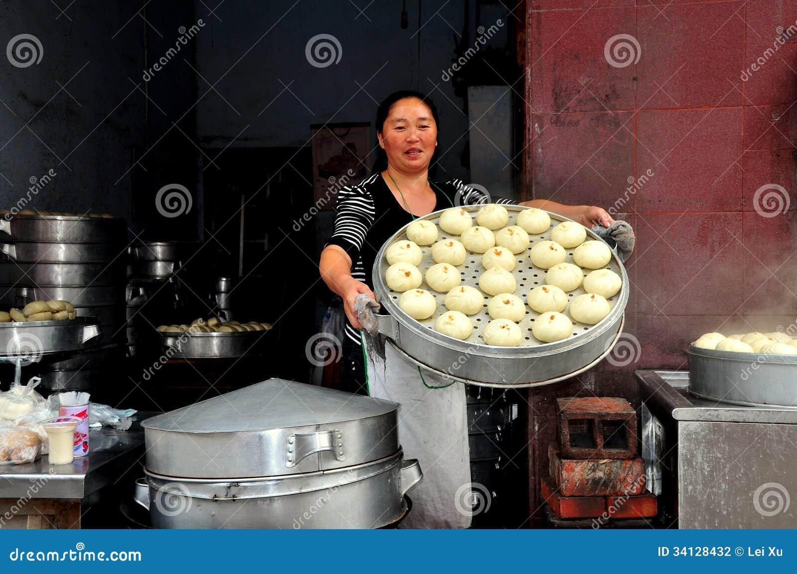 Pengzhou, China: Mujer con Bao Zi Dumplings cocido al vapor