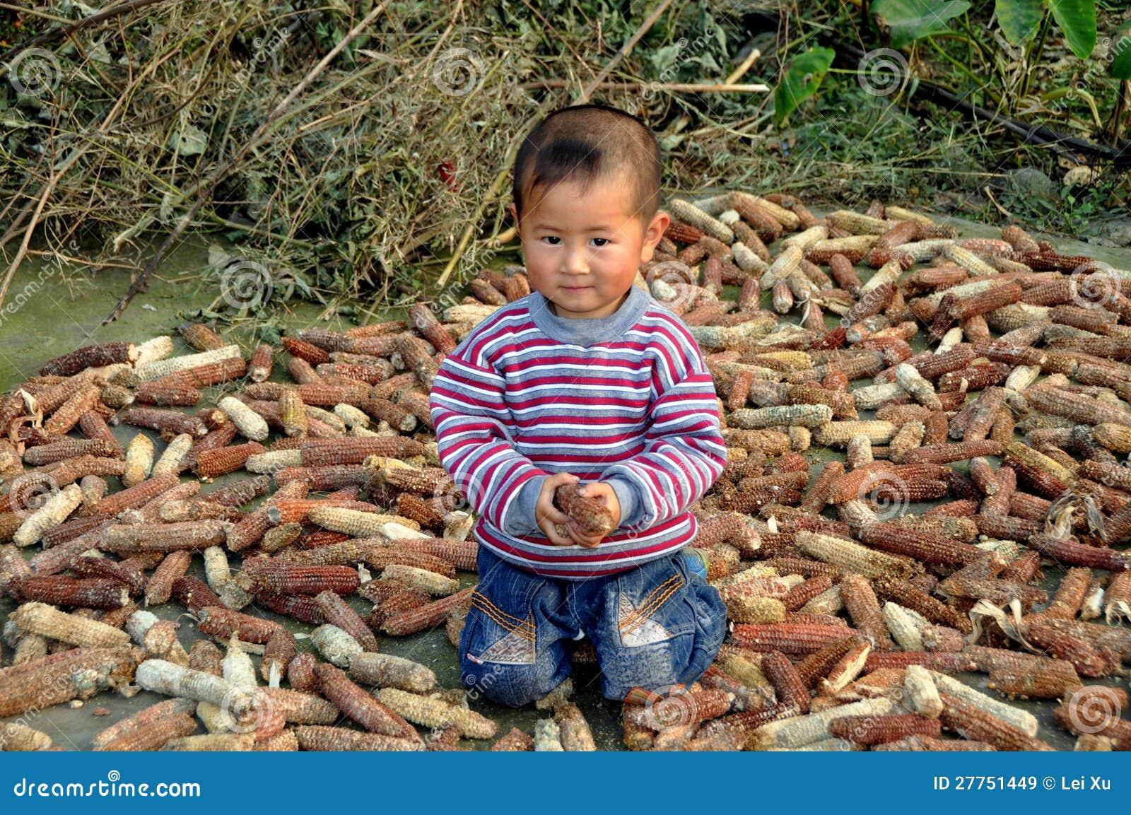 Pengzhou, Chine : Enfant avec des épis de maïs