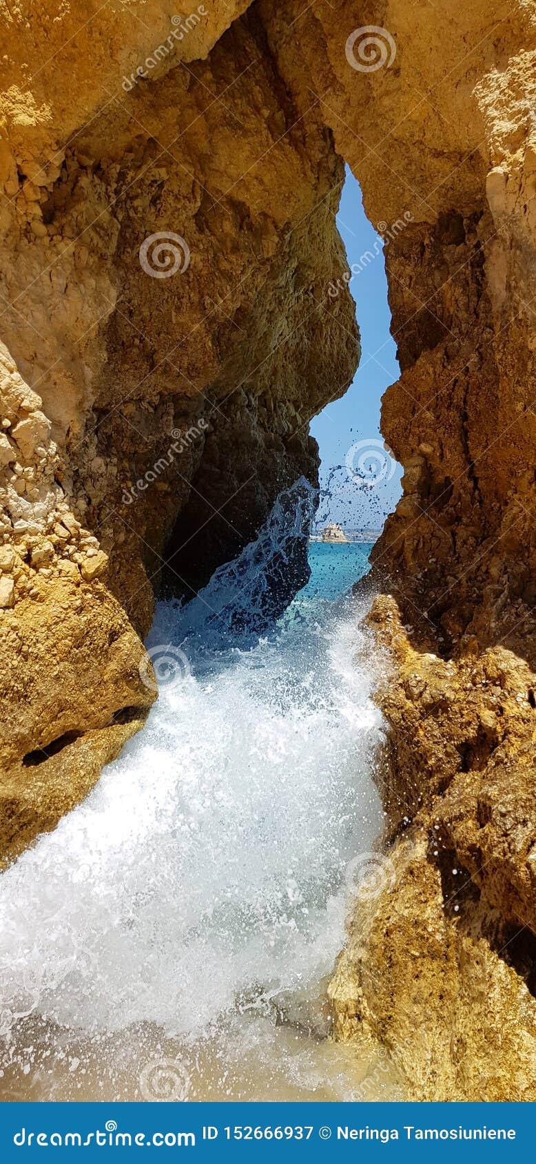Penhascos bonitos na turquesa Oceano Atlântico perto do Praia Dona Ana da praia, Lagos, Portugal