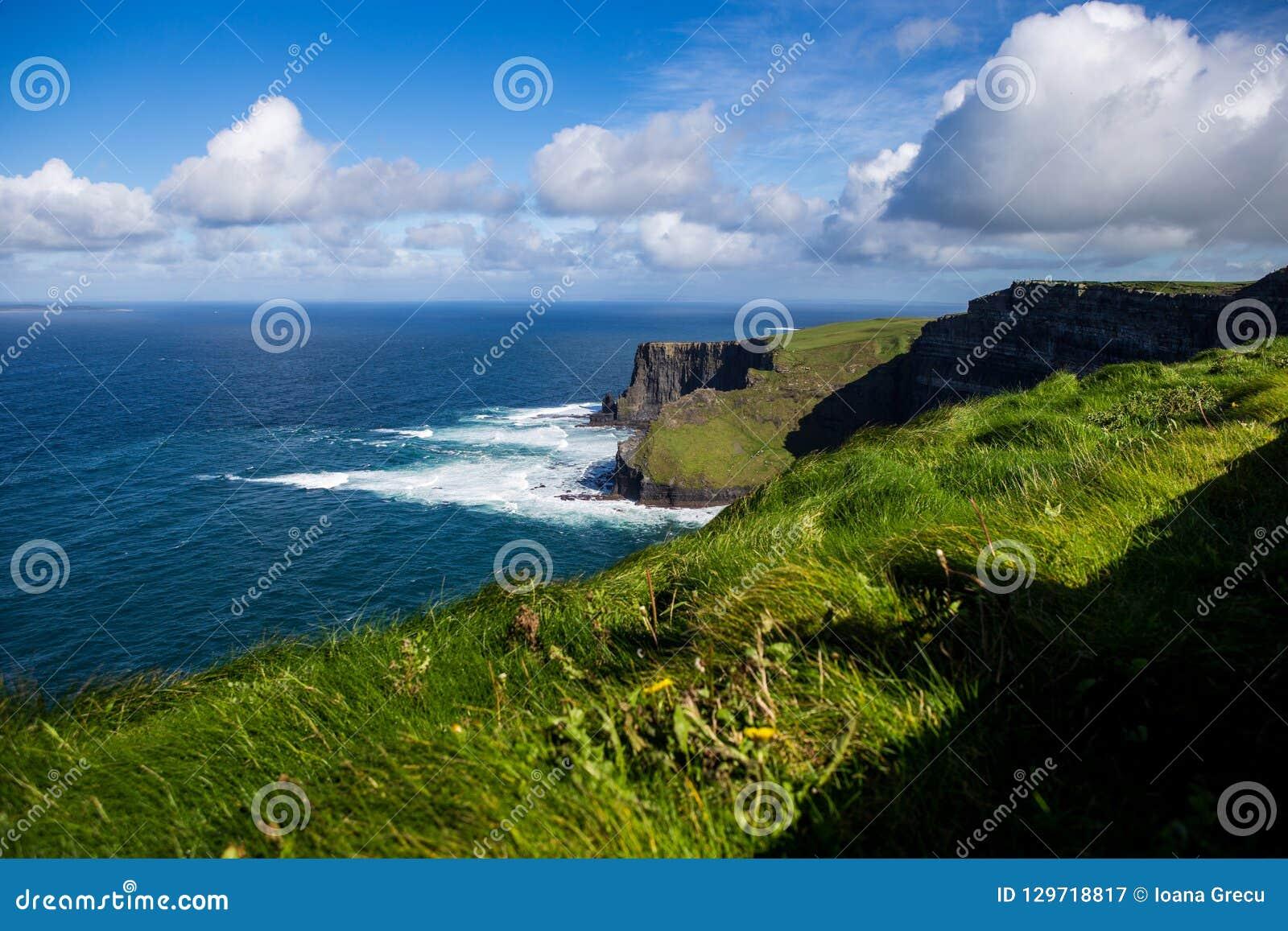 Penhascos de Moher no oceano de Alantic na Irlanda ocidental com as ondas que golpeiam contra as rochas