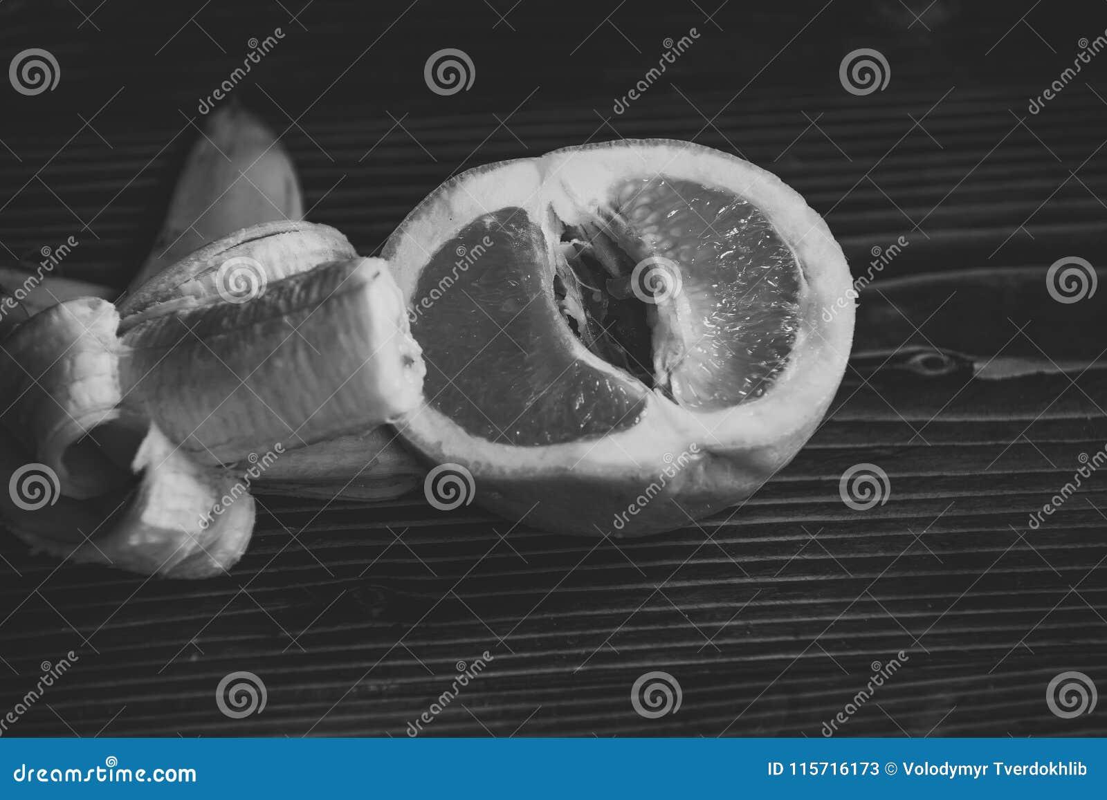 Penis och slida, banan med den gula peelen i röd grapefrukt