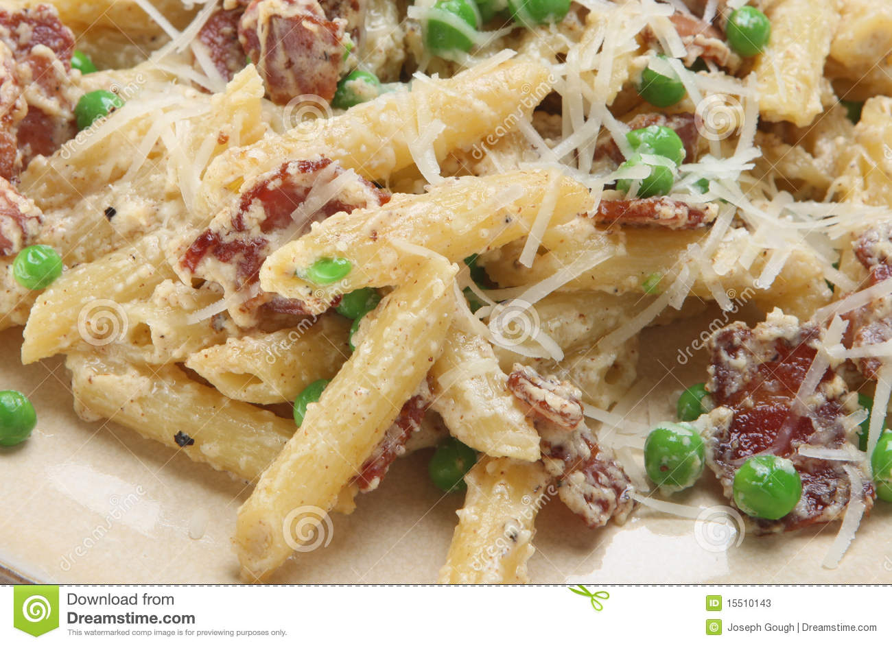 Rigatoni pasta with pancetta, ricotta cheese and peas, garnished with ...