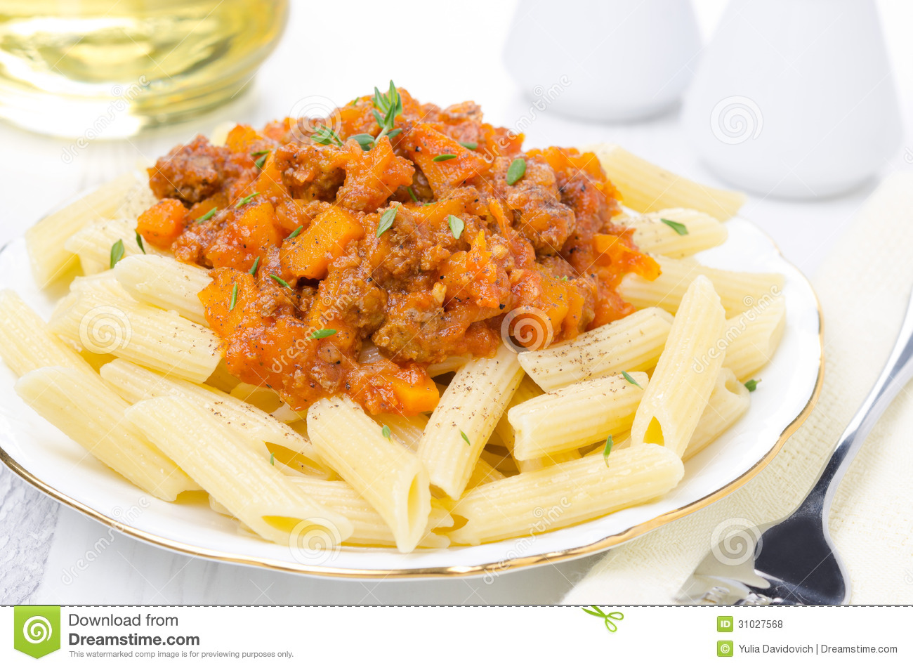 Penne pasta with sauce of beef, tomato and pumpkin on the plate close ...