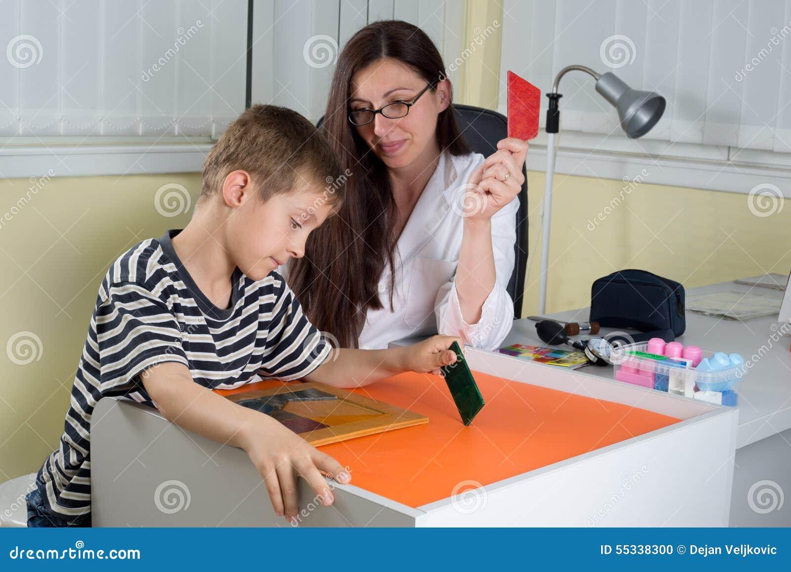 Pensée logique de docteur Examining Little Boy avec des formes géométriques colorées dans la chambre de consultation