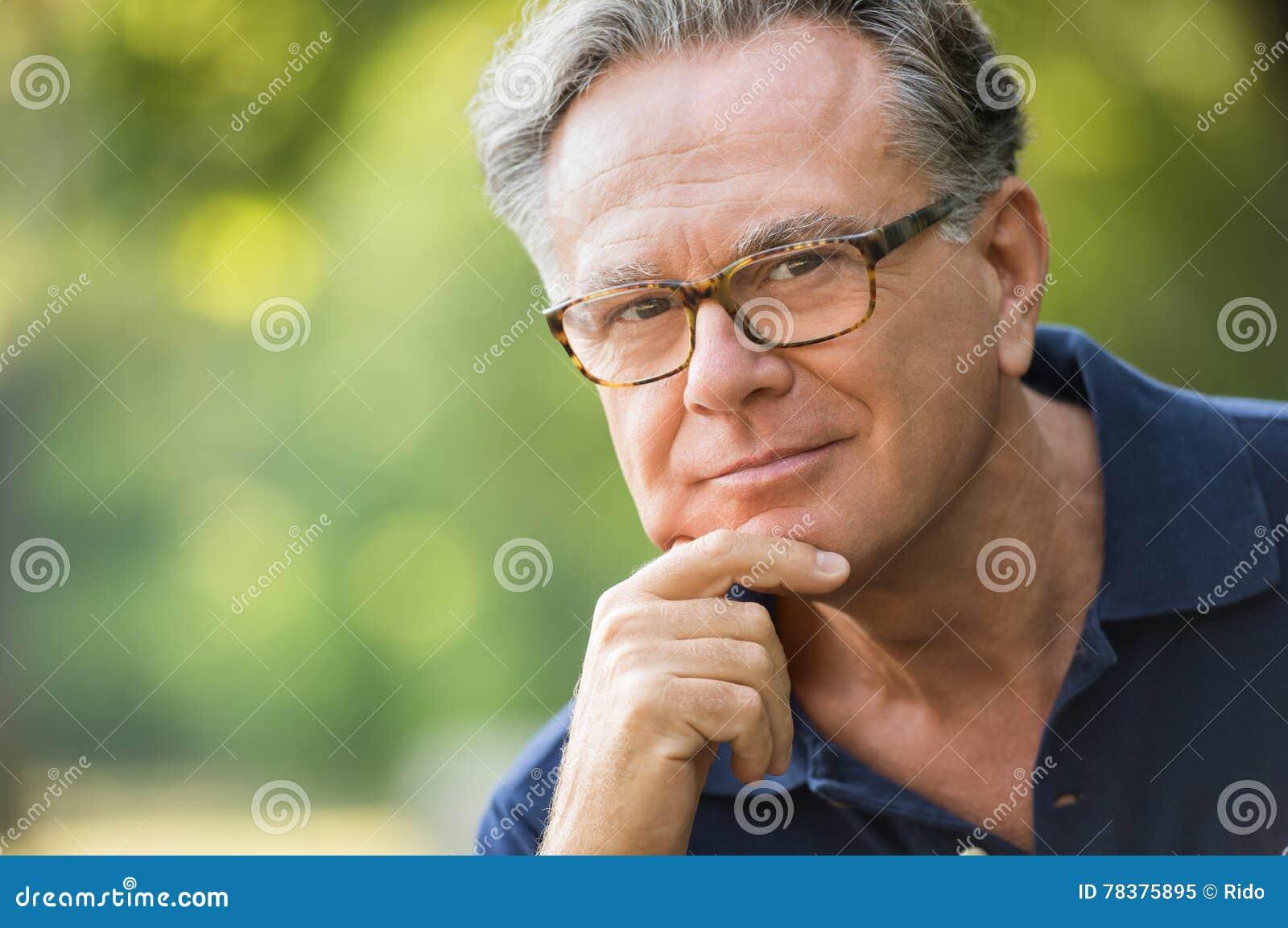 Feche acima da cara do homem superior satisfeito no parque que olha a  câmera Retrato do homem maduro que senta-se no parque com mão no queixo  Ancião de ... ddfbd83ad3b