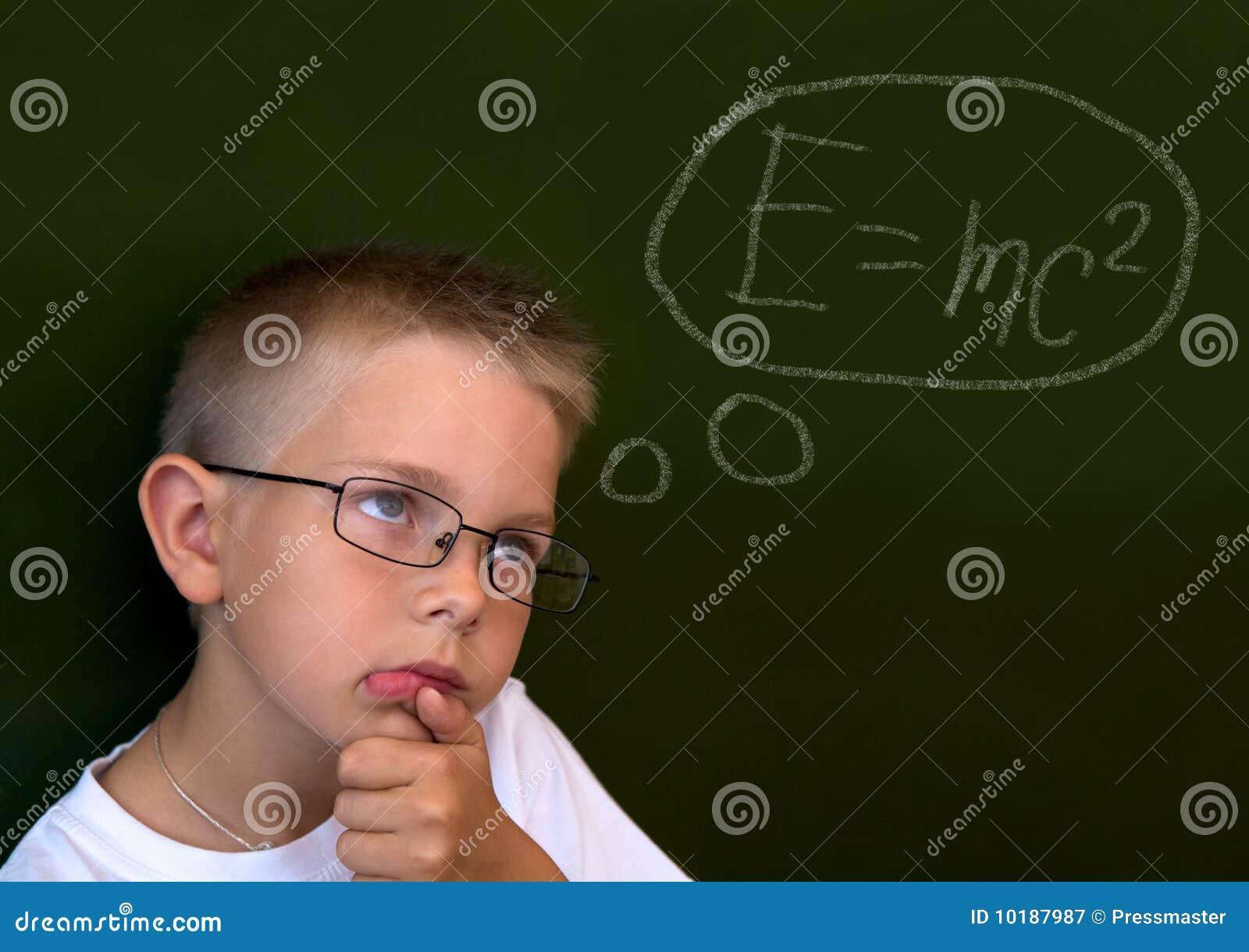 Foto del ragazzo pensive dalla lavagna che tocca il suo mento mentre