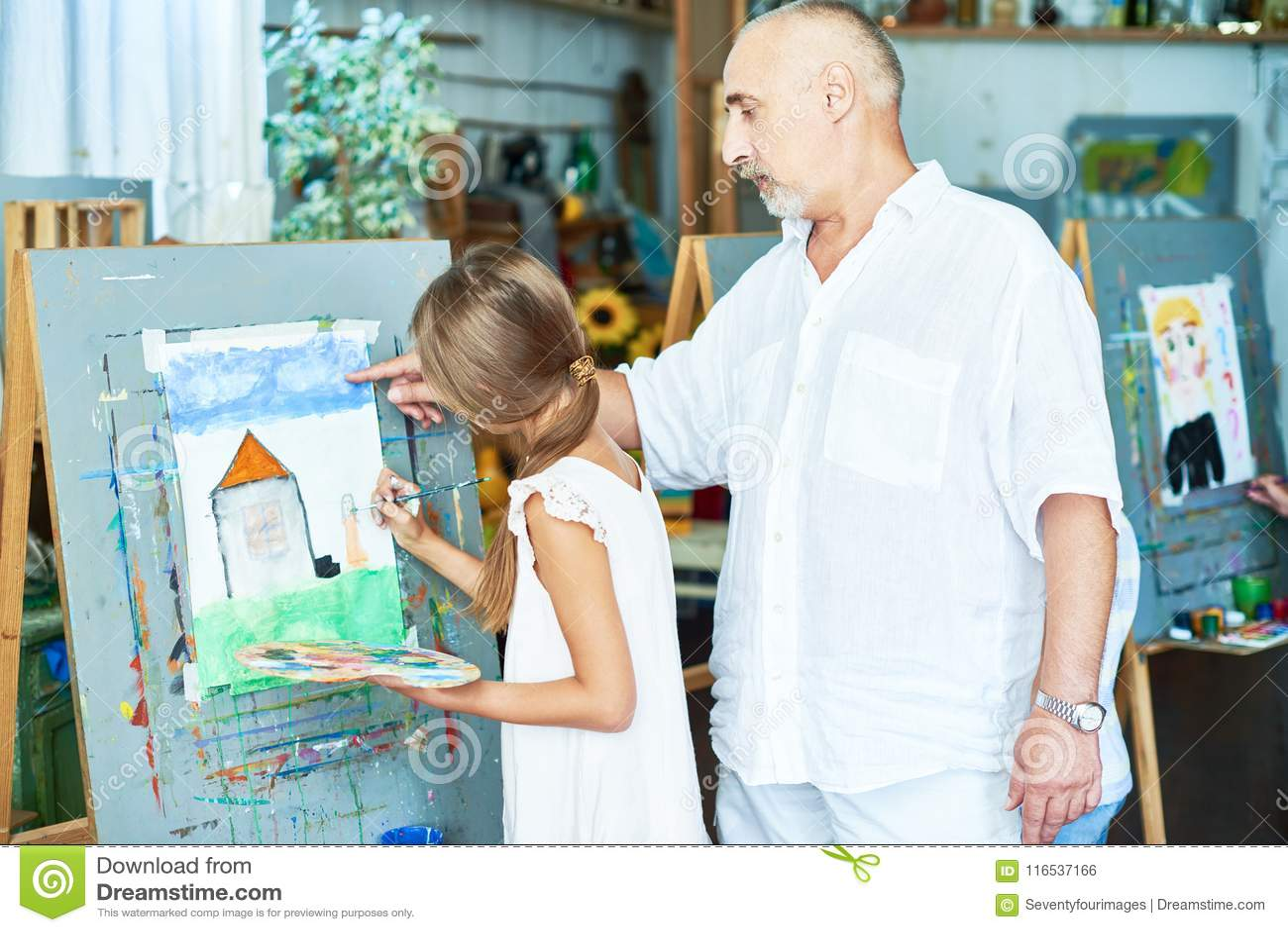 Pensionär Art Teacher Helping Little Girl i studio