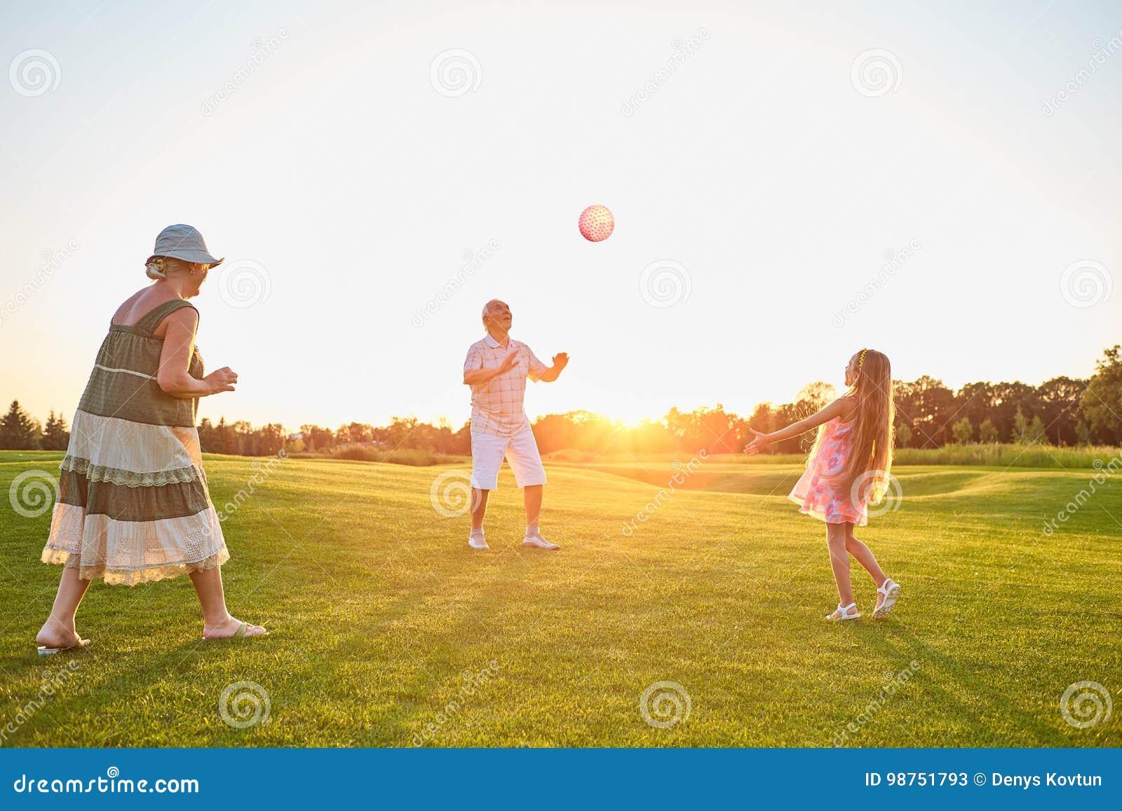 Pensionärer med barnet som spelar bollen
